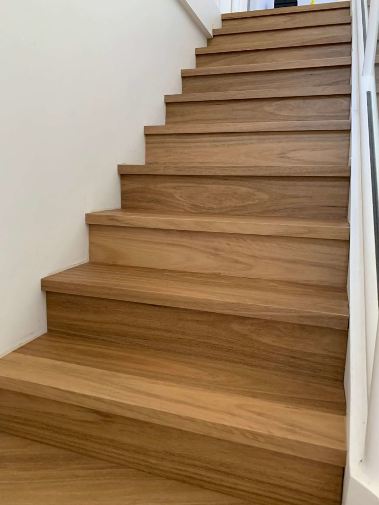 View looking up laminate stair case in Spotted Gum with white wall on the left and white ballustrade and handrail on the right.